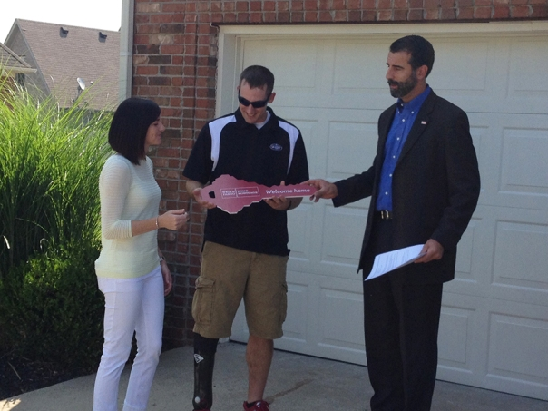 A former Army sergeant, receives key to new home